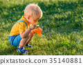 One year old baby boy blowing soap bubbles 35140881