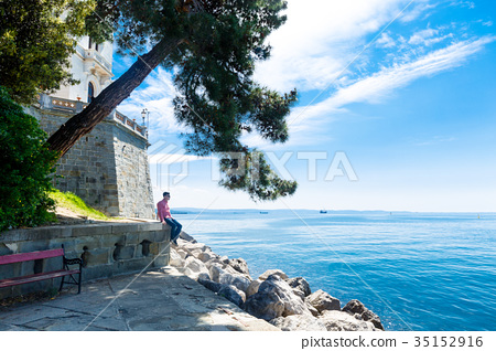 Man sits near the Miramare castle in Italy 35152916