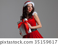 Woman in santa hat with gift 35159617