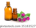 burdock oil in glass bottle and burdock flowers 35163527