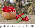 dogwood berry with leaf in bowl on wooden table 35163882