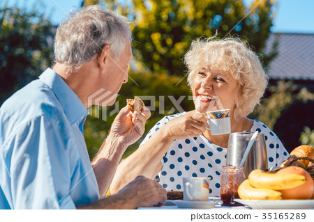 Happy elderly couple eating breakfast in their 35165289