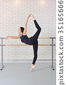 Ballerina stretches herself near barre at ballet 35165666