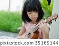 Asian girl playing the ukulele 35169144