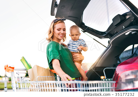 Mother with baby boy putting shopping into back of 35177232