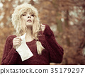 sick woman sneezing in tissue outdoor 35179297