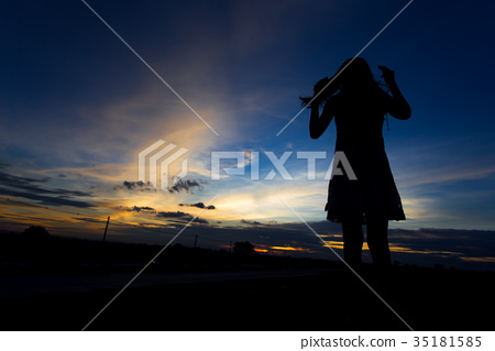Silhouette of woman posing at sunset or sunrise 35181585