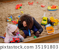 Mother playing with her daughter in a sandbox 35191803