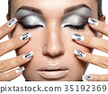 Beautiful girl with the silver makeup and nails. 35192369