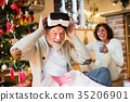 Senior couple in front of Christmas tree with VR 35206901