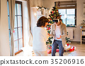 Senior couple in front of Christmas tree with VR 35206916