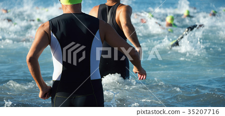 Triathletes running out of the water on triathlon 35207716
