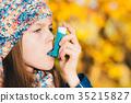 Asthma patient girl inhaling medication 35215827