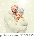 smiling couple in winter clothes hugging 35229255
