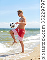 young man with ball playing soccer on beach 35229797