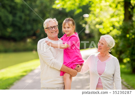 senior grandparents and granddaughter at park 35230287