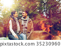 happy couple sitting on bench near camp fire 35230960