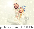 smiling couple in winter clothes hugging 35231194