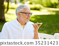 old man using voice command recorder on smartphone 35231423