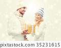 smiling couple in winter clothes with gift box 35231615