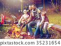 family with smartphone taking selfie near campfire 35231654