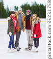 friends holding hands on outdoor skating rink 35231758