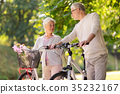 happy senior couple with bicycles at summer park 35232167