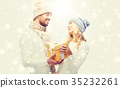smiling couple in winter clothes with gift box 35232261