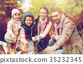 happy family roasting marshmallow over campfire 35232345