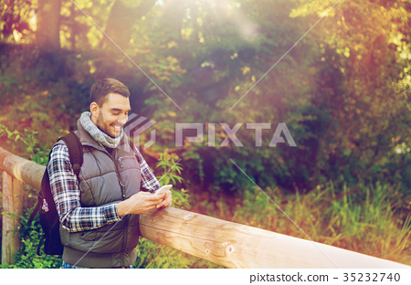 happy man with backpack and smartphone outdoors 35232740
