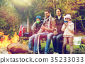 happy family sitting on bench at camp fire 35233033