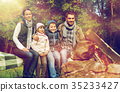 happy family sitting on bench at camp fire 35233427