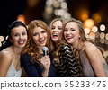 women with microphone singing karaoke at christmas 35233475