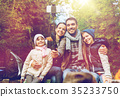 family with smartphone taking selfie near campfire 35233750