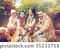 happy family roasting marshmallow over campfire 35233758