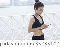 运动服的妇女听到音乐的 35235142