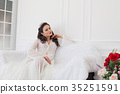 bride in wedding dress sitting on a couch 35251591