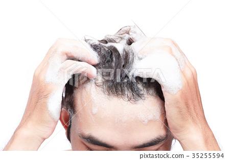 Closeup young man washing hair with white  35255594