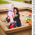 Mother playing with her daughter in a sandbox 35295830