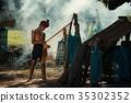 Asian fisherman make wicker fishing equipment. 35302352