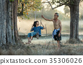 Children with farter are playing swings in rural. 35306026