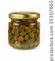 Small jar of pickled green capers over white 35307665