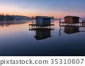 A small lake with fisherman's hut at sunrise 35310607