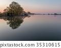A small lake with fisherman's hut at sunrise 35310615