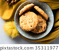 Mug of tea with milk and cookies in winter scarf 35311977