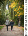 women back walking in parc with maple trees 35313238