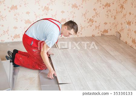 Handyman Laying Down Laminate Flooring Boards Stock Photo