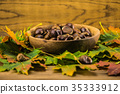 autumn leaf and   chestnuts on  wooden table 35333912