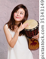 Asian American woman playing African hand drum 35343149