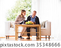 Health visitor and a senior man with tablet during 35348666